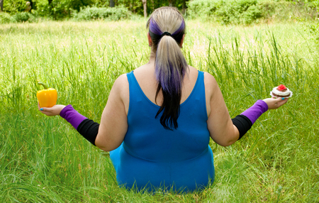 Fat woman wants to lose weight diet view from behind sits on grass image man figure in blue suit bush tree holding in hands yellow sweet bell pepper in right hand cake, torso purple black short nails blue on blurred background fat sport
