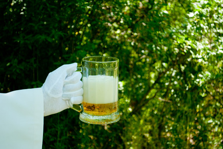 The waiters hand in a white glove and with a white napkin holding a beer-filled glass of beer filled with beer and foam on a blurred background of the nature of trees and bushes