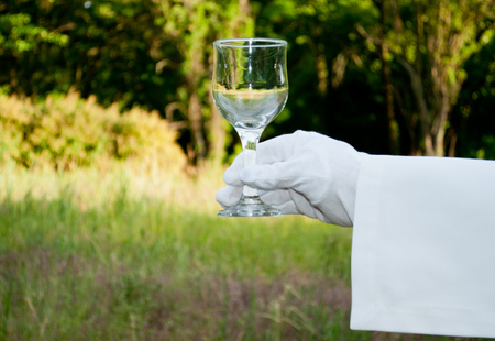 Hand of the waiter in a white glove and with a white napkin holding a glass for a wine on a blurred background of nature green bushes and trees
