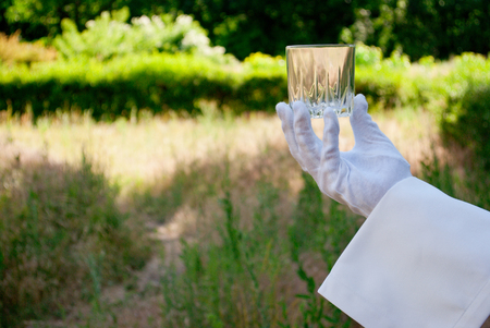 Hand of the waiter in a white glove and with a white napkin holding an empty glass glass on a blurred background of nature green bushes and trees Stock Photo