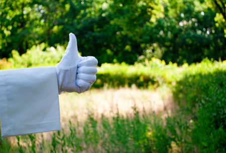 The waiters hand in a white glove and with a white napkin shows with the fingers a sign on the background of trees on a background of trees and bushes on a blurred background
