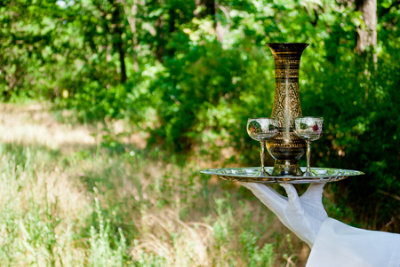 A waiters hand in a white glove and a white napkin holding a metal table set with two wine glasses and a decanter of metal on a blurred background of nature green bushes and trees