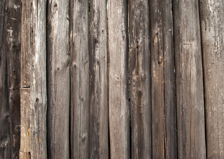 Wooden gray natural tree trunks palisade fence in Ukrainian style from a tree closeup background Stock Photo