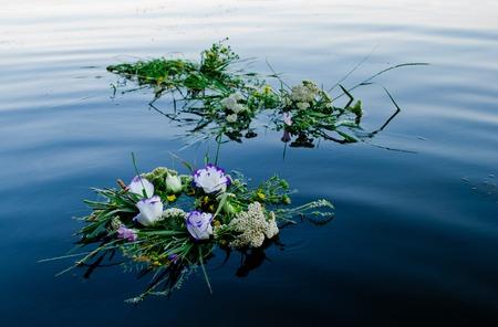 白紫黄色の美しい新鮮な花々 と緑の草イヴァンクパーラの饗宴のための穏やかな水に沿ってウクライナ川ドニエプル川に沿って浮遊の花輪の 3 つの