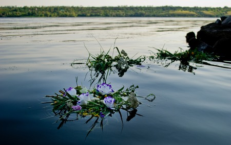 Three beautiful large bouquet of wreaths of white purple yellow beautiful fresh wildflowers and green grass floating along the Ukrainian river Dnieper along the calm water for the feast of Ivan Kupala