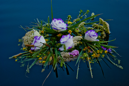 One beautiful large bouquet of a wreath of white purple yellow beautiful fresh wildflowers and green grass floats along the Ukrainian river Dnieper along calm water for the feast of Ivan Kupala Stock Photo