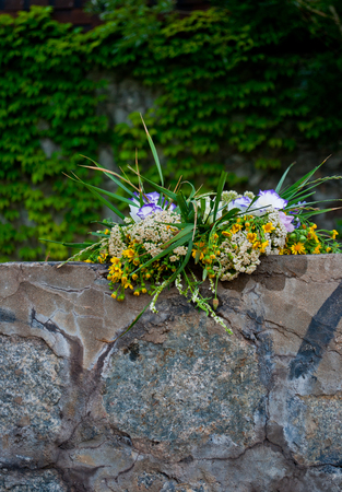 One beautiful big bouquet of a wreath of white purple yellow fresh wildflowers and green grass lying on the rocks of a parapet wall of rocks on a background of stone wall on the feast of Ivan Kupala