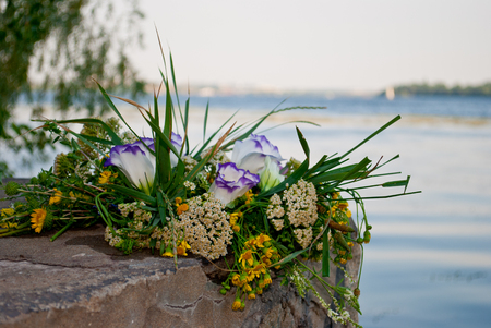 One beautiful big bouquet of a wreath of fresh wildflowers and green grass lying on the rocks of a parapet wall of rocks against the background of the Ukrainian river Dnepr on the feast of Ivan Kupala