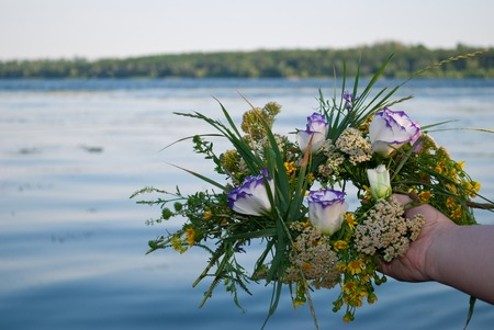 One big beautiful bouquet of a wreath of wildflowers with yellow white and purple flowers and green grass is held by a female hand girl over a river in the evening holiday of Ivan Kupala