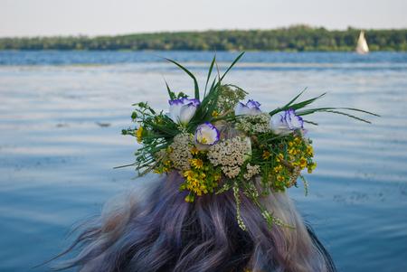 Een grote mooie boeket krans van wilde bloemen en groen gras op het hoofd van het meisje haar blonde over het water rivier in de avond vakantie van Ivan Kupala tegen de witte zeilen schip achtergrond