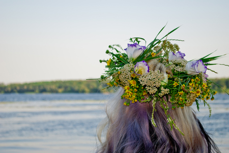 One big beautiful bouquet wreath of wild flowers with yellow white and purple flowers and green grass on the head of the girl hair blonde over the water river in the evening holiday of Ivan Kupala Stock Photo
