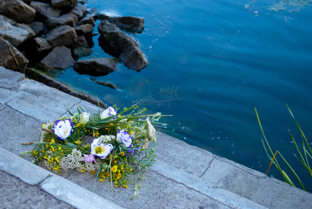 One large beautiful bouquet of wreath of wild flowers, a green grass on the back of the river