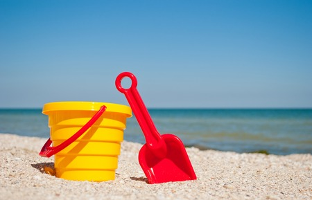 Yellow childrens bucket with red toy toy plastic red scapula on the left by the blue sea and blue sky yellow sand beach sea shore seashells summer vacation sunny summer day, bright sun, baby toys