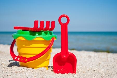 Eimer der gelbe Kinder mit rotem Griff, rote Spachtel und Rechen des Plastiks, grünes Sieb, blaues Meer und Himmel gelbes Sand setzen Strandstrand-Seashells-Sommerferien sonnigen Sommertag, helle Sonne, Spielwaren der Kinder auf den Strand Standard-Bild - 86028711