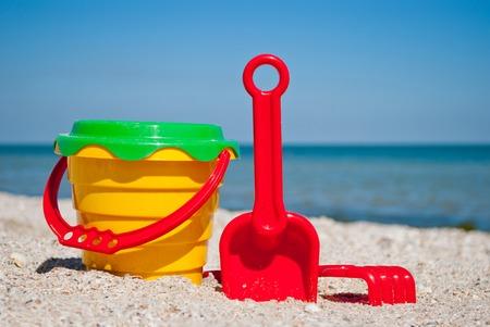 Eimer der gelbe Kinder mit rotem Griff, rote Spachtel und Rechen des Plastiks, grünes Sieb, blaues Meer und Himmel gelbes Sand setzen Strandstrand-Seashells-Sommerferien sonnigen Sommertag, helle Sonne, Spielwaren der Kinder auf den Strand Standard-Bild - 86028712