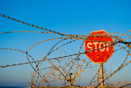 a large red road prohibiting stop sign stands on a deserted beach in front of him fence of metal wire fence