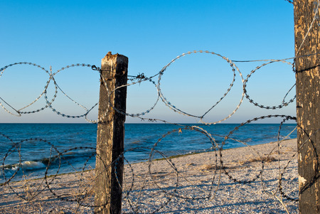 barbed wire mesh of metal and pillars of wood protects a deserted beach fence passage banned yellow sand blue sea shore clear blue sky summer warmth