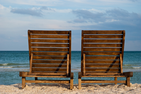 two wooden brown chaise longue on the beach on the blue sea shore water blue sky sea wave beautiful landscape summer vacation beach sand weekend rest