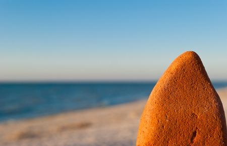 Pierre lumineuse orange à droite, contre la mer bleue, sable jaune, rivage ciel bleu clair, chaleur estivale