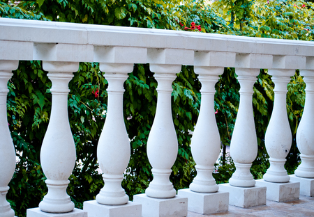 White marble columns in a row, parapet, fence, against the background of green flowering bushes, flowers, in the shade, architecture, olden time, fence, vintage, art