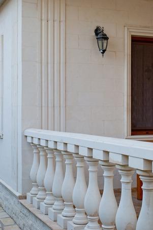 Witte marmeren kolommen op een rij, borstwering, hek, tegen een achtergrond van een marmeren muur, wandlamp, venster, straatlantaarn, architectuur, olden, hek, vintage, kunst