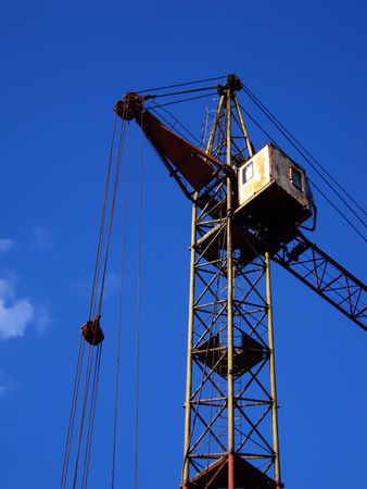 erecting: Building crane erecting houses with blue sky as the background