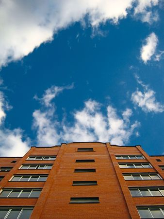 residental: Residental building made of brick lit by sun with blue sky and clouds passing