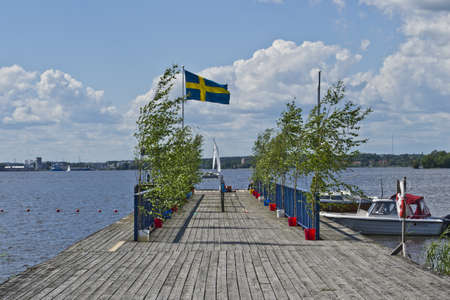 wharf with Swedish flag in summerday Stock Photo