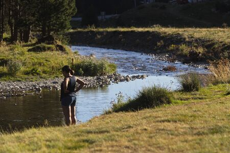 Llanos del hospital, Huesca/Spain; Aug. 21, 2017. A woman relaxes by the river. Place called Llanos del Hospital belonging to the municipality of Benasque in the heart of the Pyrenees.