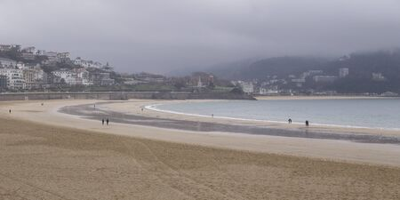 Donostia, Gipuzkoa/Basque Country; Dec. 28, 2018. People strolling at low tide along La Concha beach in Donostia-San Sebastian Фото со стока