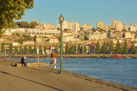 Porto, Portugal; Aug. 02, 2012. Fishermen on the banks of the Douro river as they pass through the city of Porto. 写真素材