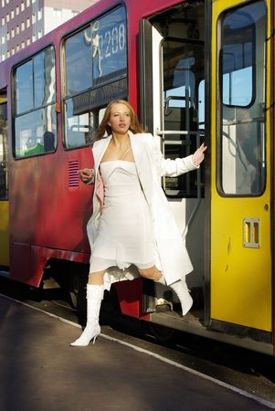 The girl jumps from a tram on the move.  Stock Photo
