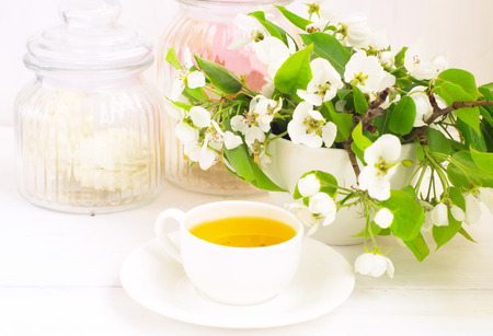 pastila:                 Cup of tea is standing on the wite table with apple flowers                Stock Photo