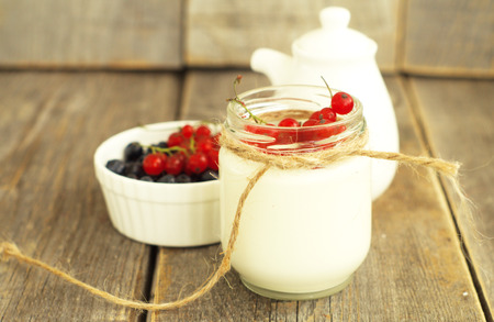 nonfat:                                       nonfat yogurt with red currant  and blueberry on the wooden background