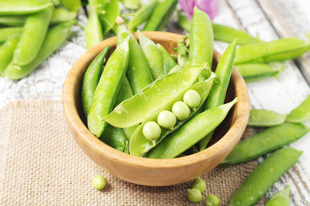 bawl: Fresh green pea pods in the bawl on the wooden table