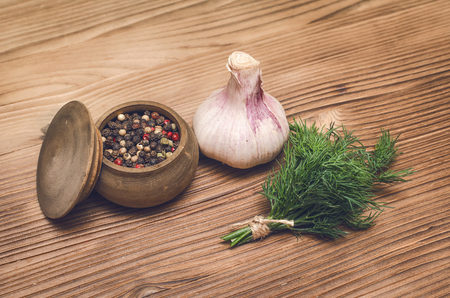Garlic bulb, pepper peas in the bowl and dill greenery on brown wooden table background. Organic ingredients.