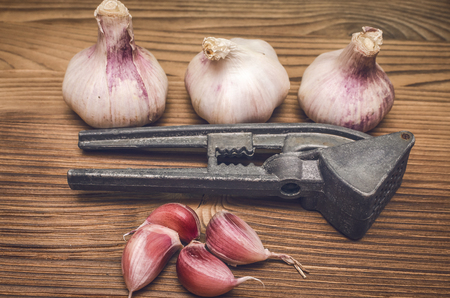 Garlic bulb and garlic press on brown wooden table background close up photo.