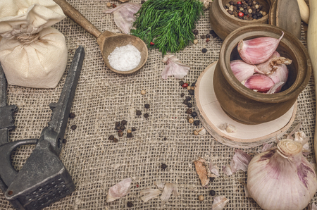 Garlic bulb and cloves, pepper peas, salt, greenery dill on the brown wooden table background. Different Spices. Ingredients for marinade.