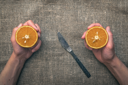 Cut orange in the man hands on the burlap sackcloth table background. First-person photo.