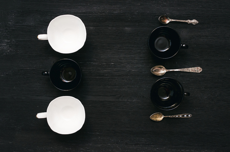 Black and white tea or coffee empty cup and set of silver spoons on black wooden table background.
