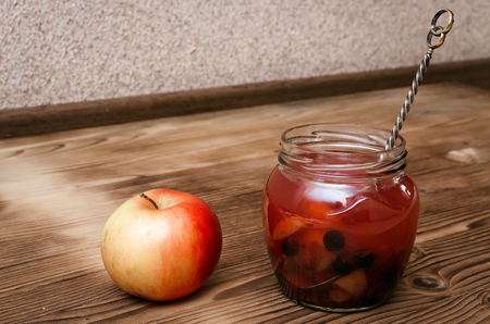 Compote stewed fruit drink in the glass bank with fresh apple on table. 免版税图像