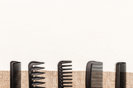 Set of black plastic hair comb on burlap cloth on white wooden surface with copy space. Barber hairdresser work desk table concept.
