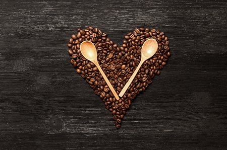 Coffee beans made in heart shape form and wooden spoons on black wooden surface background with copy space. Love of coffee concept.