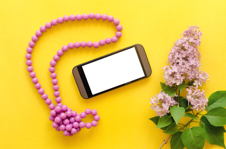 Blank screen mobile phone, beads bijouterie and lilac flowers isolated on yellow background. Reklamní fotografie