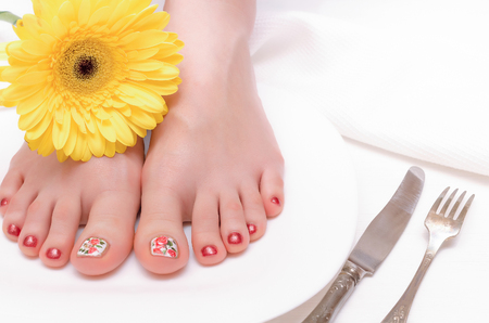 Female feet on a plate and yellow gerbera daisy flower on the white wooden background.