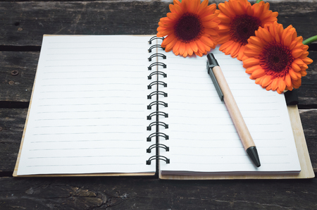 Blank page notepad and orange gerbera flowers on wooden background.