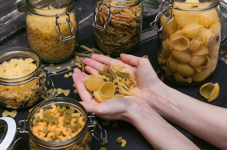 Different kinds of pasta in female hands.