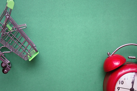 Shopping cart and red alarm clock isolated on color background. Time to shop.