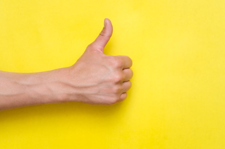 Male hand showing a thumbs up gesture isolated on yellow background.