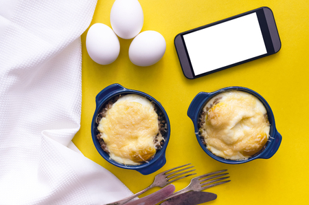 Buckwheat porridge with cheese and egg and blank screen mobile phone. Healthy food.